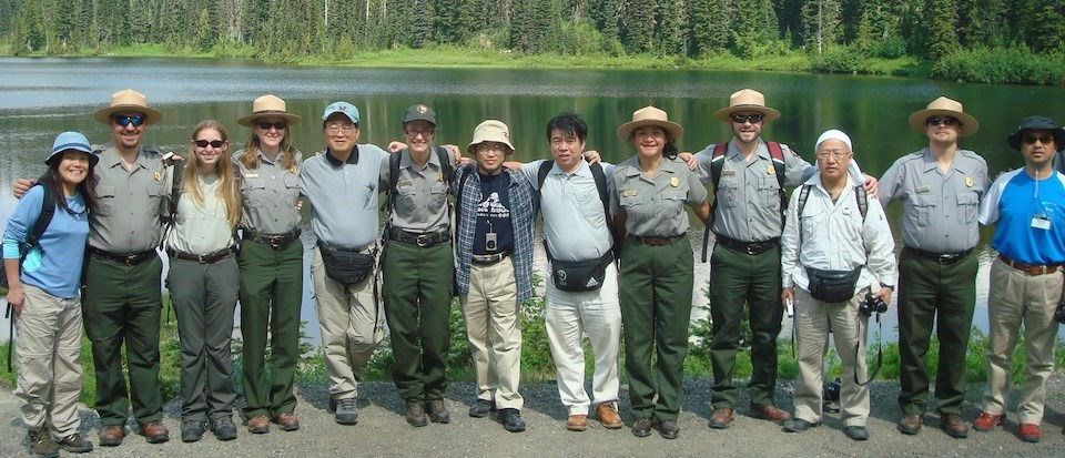Several people stand in a row with their arms around each other, some Japanese, some dressed as park rangers.