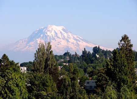 Mount Rainier in the distance rises above houses on a hill.