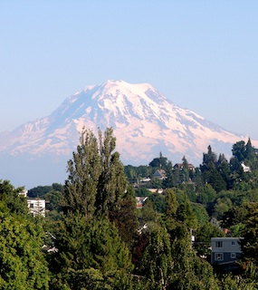 A view of Mount Rainier from Tacoma, WA with houses in the foreground.