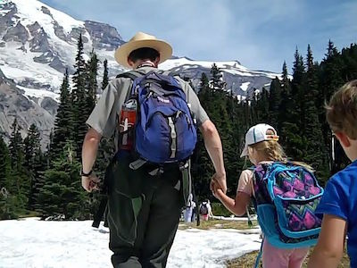 A ranger holds the hand of a girl as they make they're away across snow in a subalpine meadow.