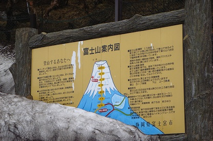 A Japanese wayside about Mount Fuji partially covered by snow.