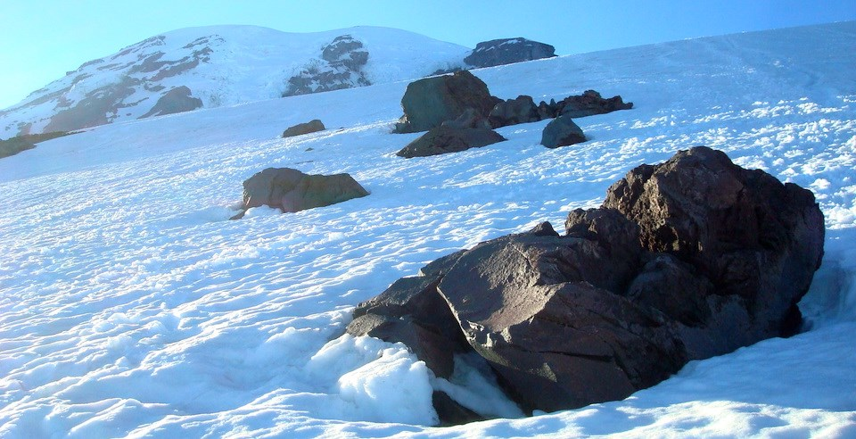 Large boulders sit on the surface of a glacier on a steep slope.