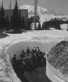 Historic photo of early visitors to Mount Rainier, pictured on an old fashioned car between high snow banks.