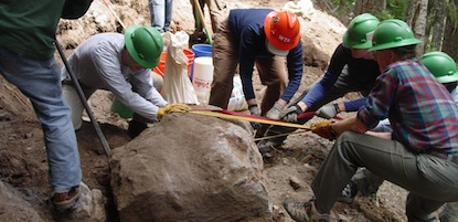 A group of volunteers using rope and a crowbar to move a large boulder from a trail at Mount Rainier National Park.