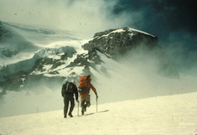 Two people walking across a snow slope with full packs
