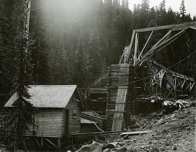 A wooden building and conveyor chute with forest in the background
