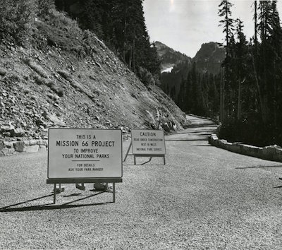 "A mountain road with a sign: ""This is a Mission 66 project"""