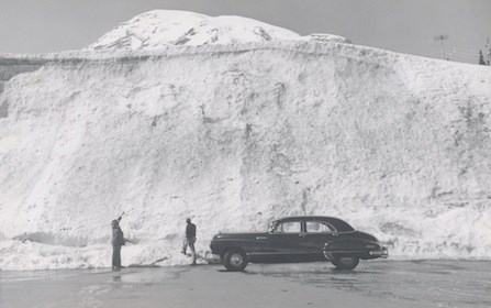 Early park visitors marvel at a snow bank at Paradise, with Mount Rainier in the backdrop.