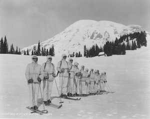 A dozen men in white uniforms on the snow with skis