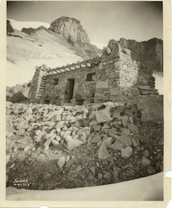 A black and white photo of a stone building on a rocky, snowy slope.