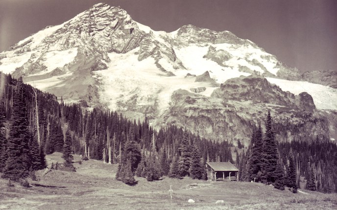 Black and white photo of Mount Rainier with tiny log cabin tucked amid the firs at the base of the mountain.