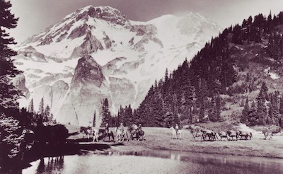 A string of horseback riders circle a subalpine lake with Mount Rainier rising in the background.