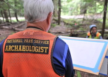"Man wearing orange safety vest with ""National Park Service Archaeologist"" on the back looks at a board with surveying paper taped to it."