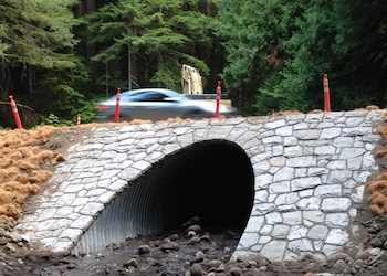 A car passes over a culvert with a restored historic rock face.