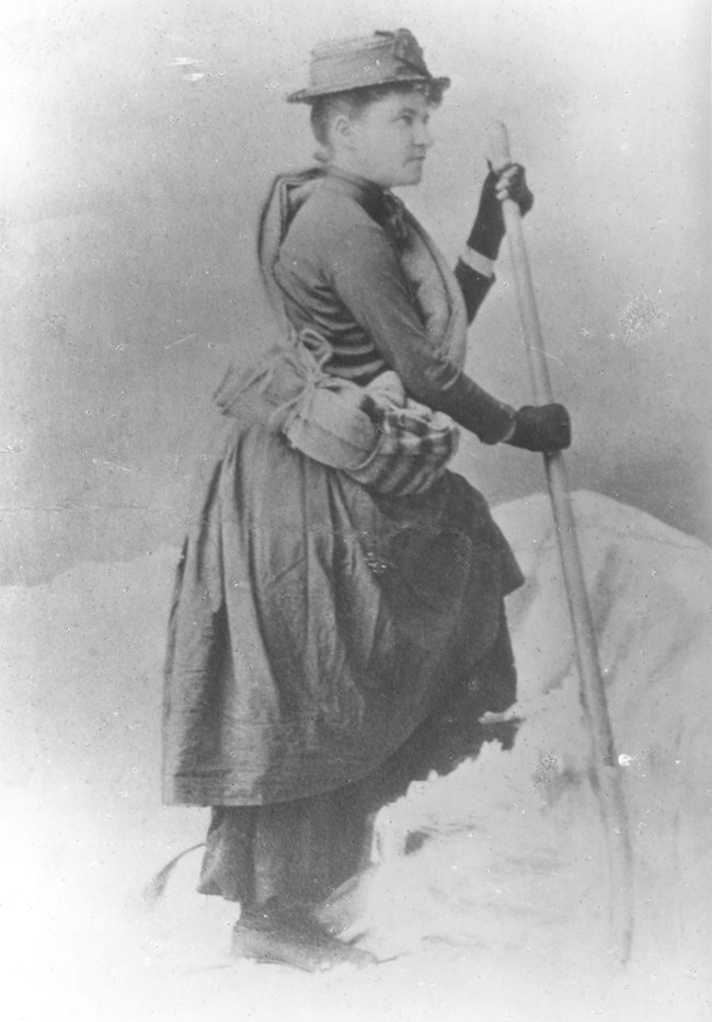 Woman wearing a dress with some climbing gear.