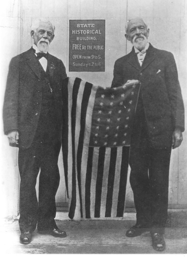 Two older men holding a United States flag between them.