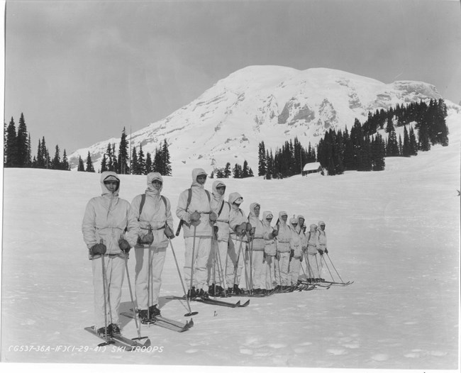 A dozen men on skis in white uniforms with Mount Rainier in the background