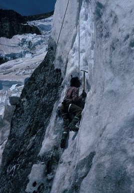 A climber is ascending a vertical glacial ice wall on Mount Rainier.