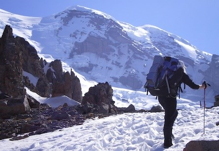 A climber with a large backpack and hiking poles walking across snow towards the rocky summit of Mount Rainier.