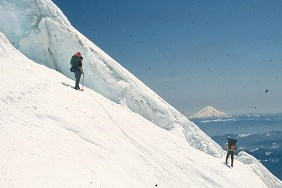 Climbers descending Tahoma Glacier with pre-1980 Mount St. Helens in the background