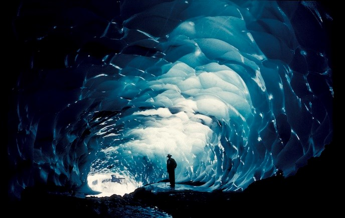 A man stands inside a dark ice cave, silhouetted by light coming from the entrance.