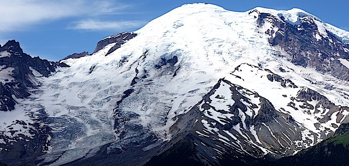 East face of Mount Rainier with views of the summit and the prominent Emmons glacier, carving a valley on the left side.