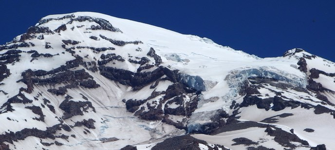 The summit of Mount Rainier with a thick glacier curling from the peak, and covered in patches of snow.