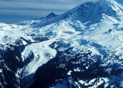 Aerial view of Mount Rainier with the Carbon Glacier curving through a narrow valley down the side of the mountain.