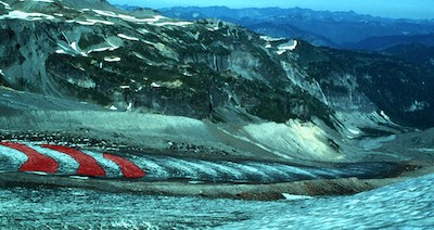 A glacier with bands of light and dark ice, with three dark bands highlighted in red, flows between rocky ridges.
