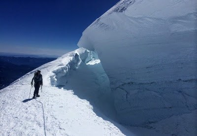 A climbing ranger stands at the edge of a large, deep crevasse on a steep slope.