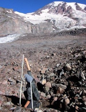 A person reaches up to measure the top of an ablation stake emerging from the rocky debris covered surface of a glacier that extends up towards the summit of Mount Rainier.