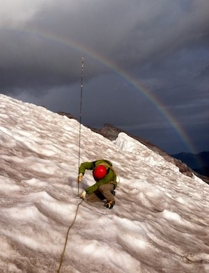 A person kneels on a glacier holding a stake with a rainbow arching overhead.