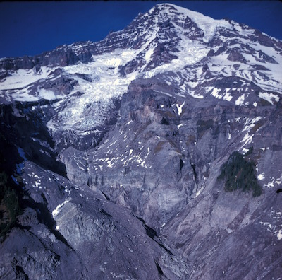 Kautz glacier near the summit of Mount Rainier flowing into a deeply eroded, steep valley.