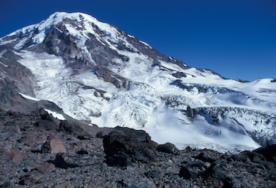 A glacier-filled valley descending from the peak of Mount Rainier, viewed from a rocky ridge.