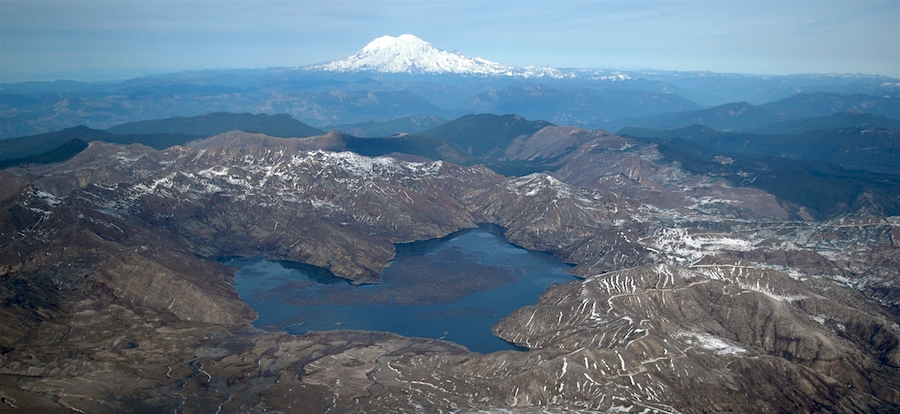 View of a lake surrounded by remains of volcanic debris flows with Mount Rainier in the distance.
