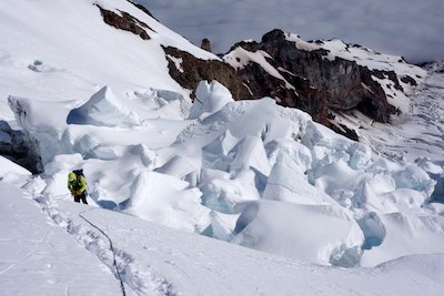 A roped-up climber ascends a snowy slope next to a section of glacier broken by seracs.