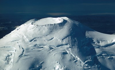 The glacier-capped summit of Mount Rainier, with the roughly circular, rocky rim of the summit crater free of ice and snow.