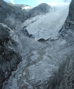 Aerial view of Carbon Glacier and the start of the Carbon River, covered in a dusting of snow.