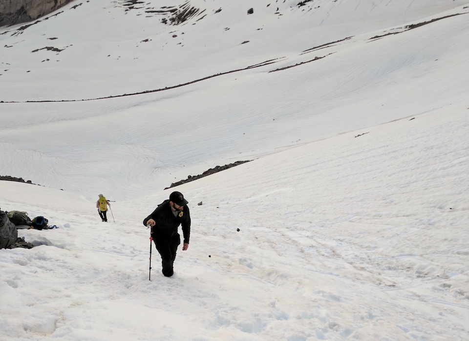 A man hikes up a steep snow covered slope.