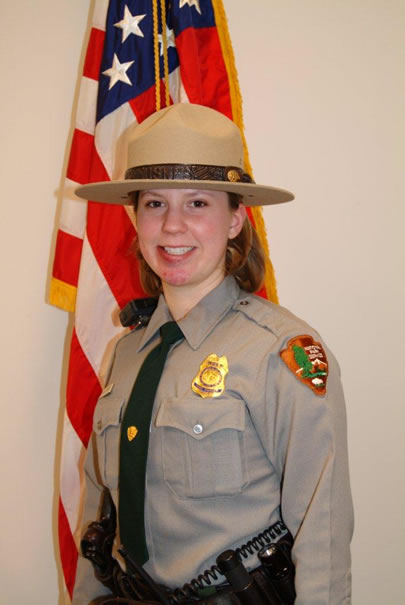 Park Ranger Margaret Anderson in her formal uniform in front of the American flag.
