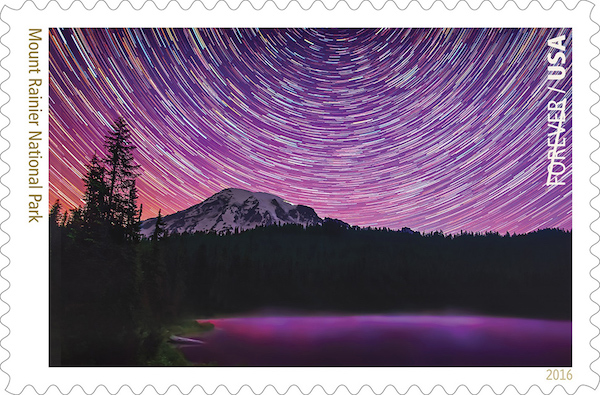 A stamp shows star trails swirling around Mount Rainier against a purple sky.