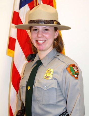 A woman in NPS law enforcement uniform in front of a US flag.