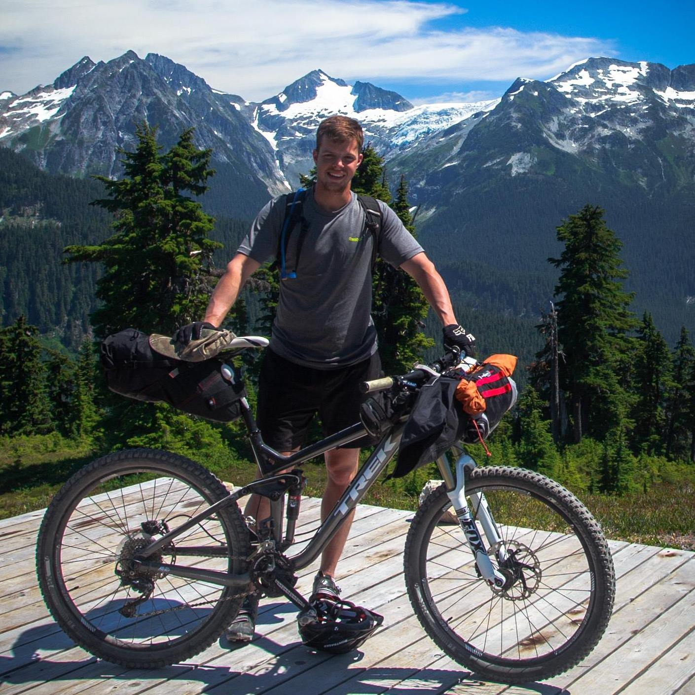 Matthew Bunker stands with his bicycle with snowcapped mountains in the background.