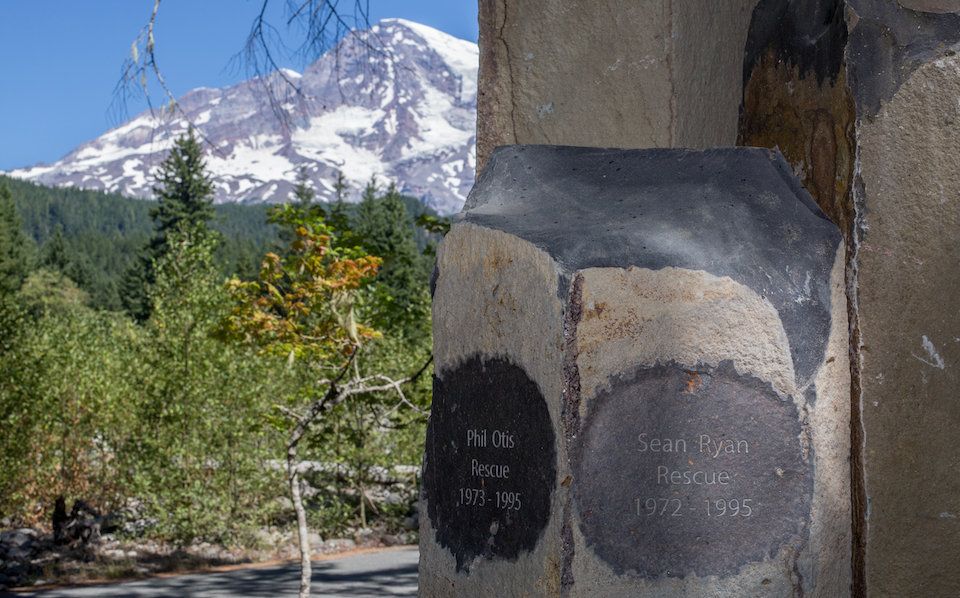 Two names inscribed into the top of a rough-hewn basalt column in front of a view of Mount Rainier.