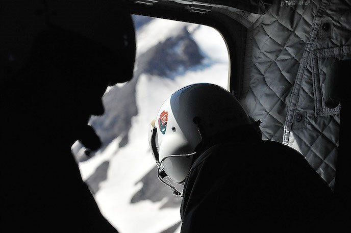 A person wearing a flight helmet with a NPS arrowhead on it leans out the open door of a helicopter.