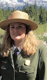 A woman with long blonde hair in an NPS uniform in front of trees