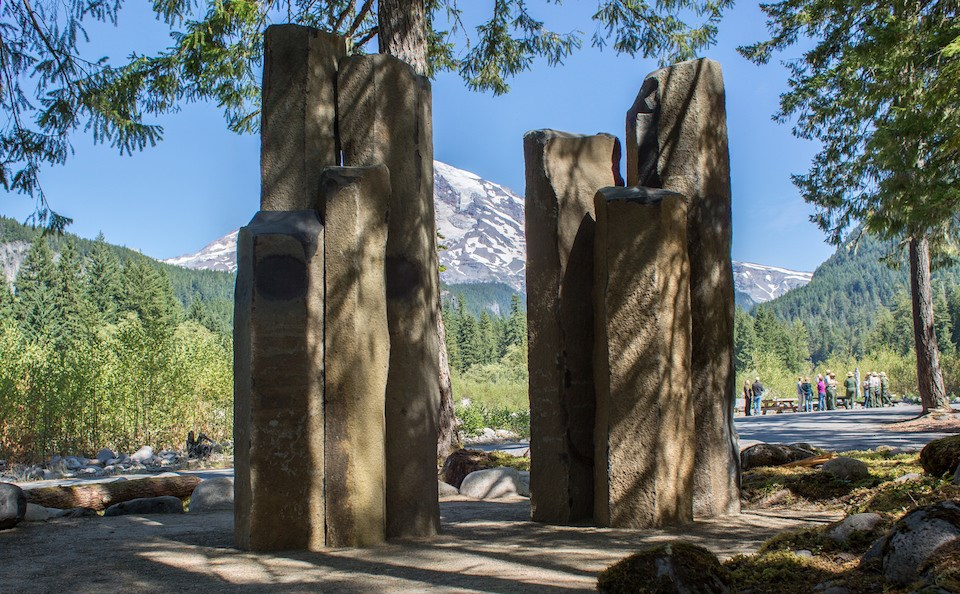 Two clusters of tall basalt columns in front of a view of Mount Rainier, shaded by trees.