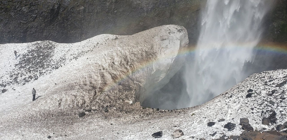 Two searchers on snow near a large hole that waterfall pours into with a rainbow in its mist.