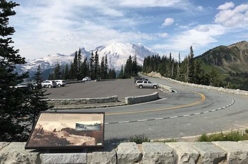 A wayside panel sits on a low rock wall that wraps borders a curved road that wraps around a small parking area with a few vehicles. The road heads away down a ridge towards a glaciated mountain peak.
