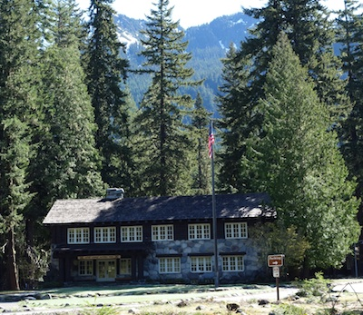 A rustic building built with rocks and timber framed by tall trees.